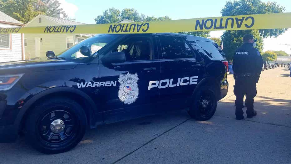 A Warren police cruiser is parked behind yellow caution tape, with an officer standing nearby.