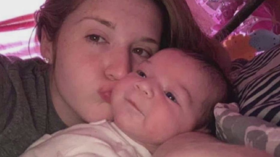 Victim Kira Seymour in a photo kissing a baby.