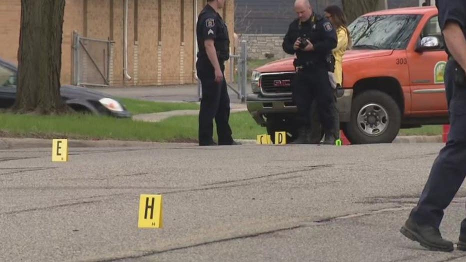 Police gather near the evidence markers Monday.