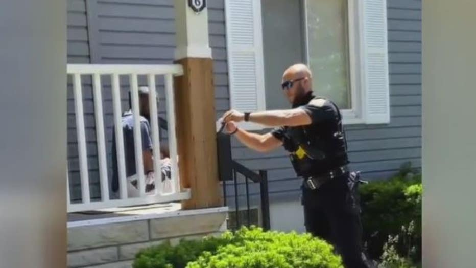 The police officer delivering the ticket to Diamond Robinson.