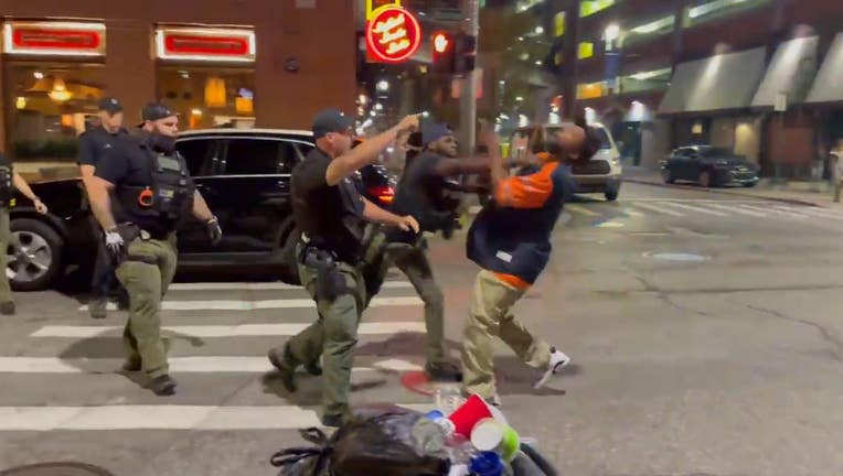 The man who was punched doesn't appear to react when officers try to lift him up. He eventually wakes up and begins shaking his hand at the police. Pedestrians then help him up as officers leave the scene.