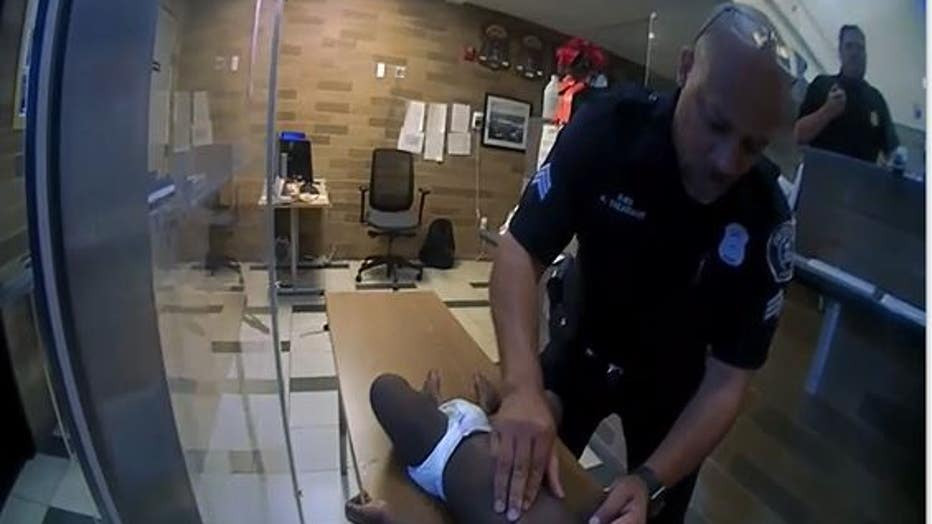 DPD Sgt. Kevin Treasvant begins chest compressions on the child. Photo still courtesy of DPD video.