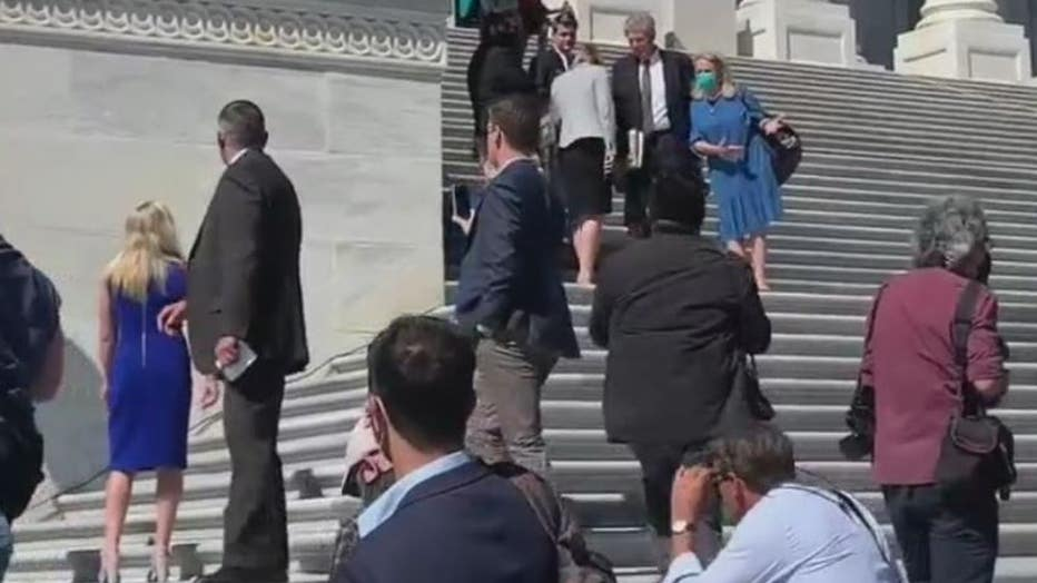Georgia Rep. Marjorie Taylor Greene (left, bright blue dress) and Michigan Rep. Debbie Dingell (light blue) can be seen on the Capitol steps today arguing abortion rights.