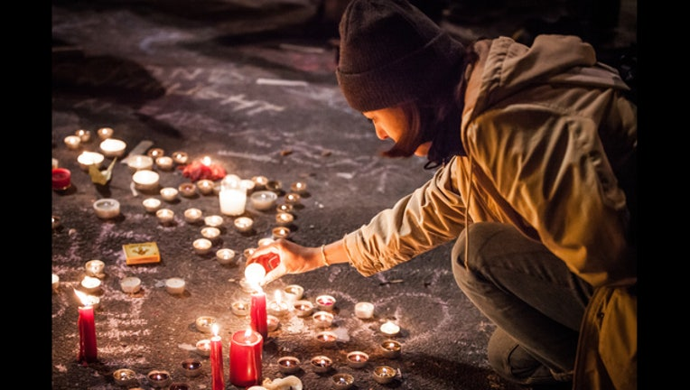 4a408c83-032216_Woman_lights_candle_Memorial_Bourse_de_Bruxelles_Brussels_Belgium_23_1458728715282-401720.jpg