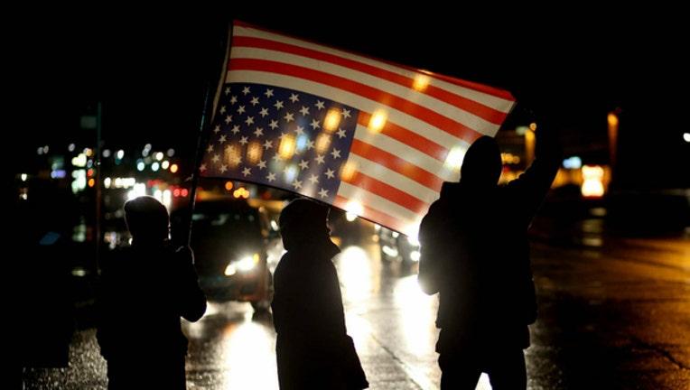 58492cb8-GETTY american flag protest_1506637836540.jpg