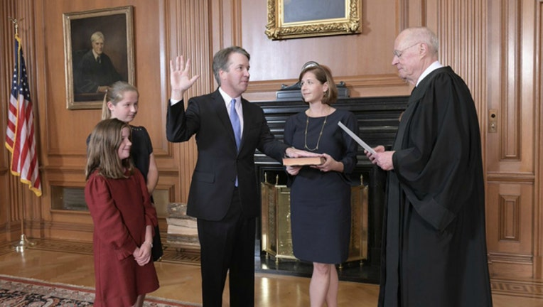 5f3d0c98-Brett Kavanaugh, surrounded by family, is sworn in as the next U.S. Supreme Court Justice.