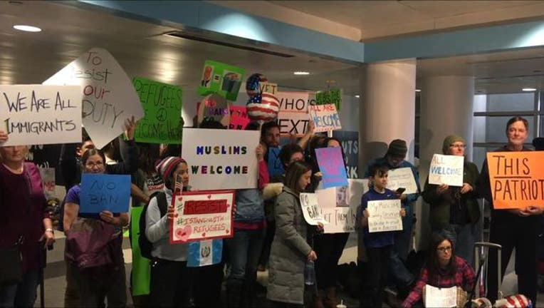 Supporters of Muslims and refugees showed up at O'Hare with welcome signs - Image Demond Miller via Fresco News