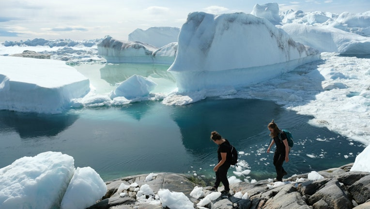 ce45e234-GETTY Visitors walk among free-floating ice jammed into the Ilulissat Icefjord during unseasonably warm weather on July 30, 2019 near Ilulissat, Greenland. _1564872238616.jpg.jpg