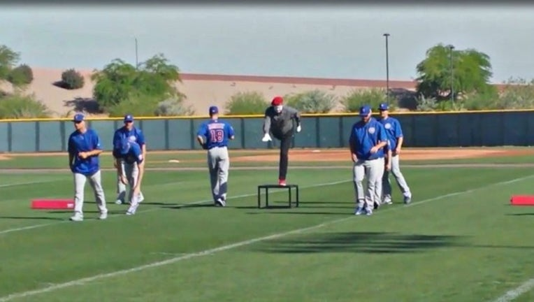 c0a7f91f-A mime helps Cubs players stretch during spring training