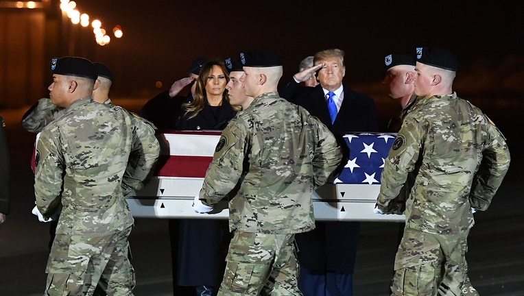 First lady Melania Trump and President Donald Trump watch as the remains of Chief Warrant Officer 2 David C. Knadle are carried during a dignified transfer at Dover Air Force Base in Dover, Delaware on November 21, 2019. (Photo by MANDEL NGAN/AFP via Getty Images)