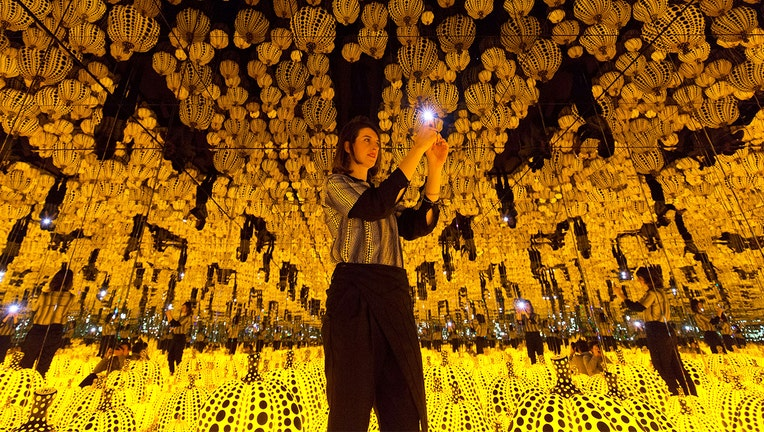 A woman poses for a photograph with an art installation entitled
