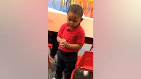 Toddler leads preschool lunch prayer before enjoying a meal with classmates