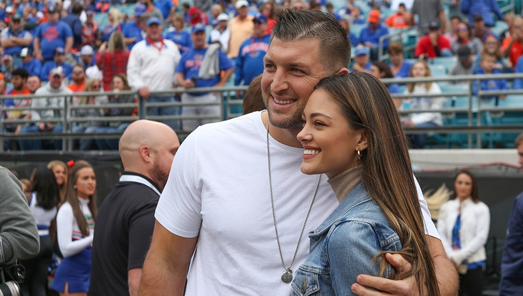 Former Florida Gators quarterback and television analysts Tim Tebow poses for a photo with fiancé Demi-Leigh Nel-Peters during the game between the Georgia Bulldogs and the Florida Gators on November 2, 2019 at TIAA Bank Field in Jacksonville, Fl. (Photo by David Rosenblum/Icon Sportswire via Getty Images)