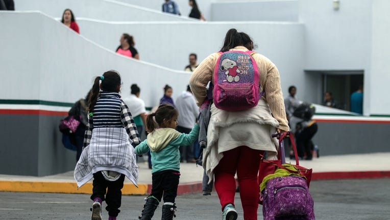 Migrants walk towards El Chaparral port of entry in Tijuana, Mexico, in the boder with the United States on June 21, 2018. - US lawmakers were poised to vote Thursday on long-term Republican-sponsored fixes to immigration amid a firestorm over family separations on the US-Mexico border. (Photo by GUILLERMO ARIAS / AFP) (Photo credit should read GUILLERMO ARIAS/AFP via Getty Images)
