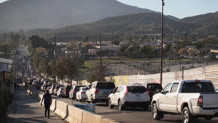 TACATE, MEXICO - JANUARY 27: Motorists heading to the United States from Mexico wait along U.S. border wall to pass through the port of entry on January 27, 2019 in Tecate, Mexico. The U.S. government had been partially shut down as President Donald Trump battled congress for $5.7 billion to build walls along the U.S. border with Mexico. Despite President Trump agreeing to end the shutdown, the debate over border wall funding continues. (Photo by Scott Olson/Getty Images)