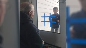Boy plays Tic-Tac-Toe with grandpa through glass door while practicing 'social distancing'