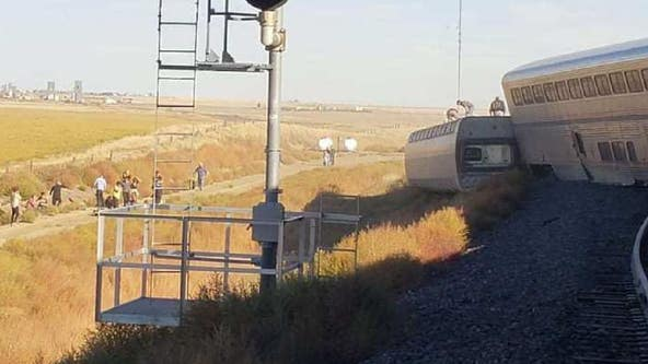 Amtrak train heading from Chicago to Seattle derails, with cars tipped over off the tracks