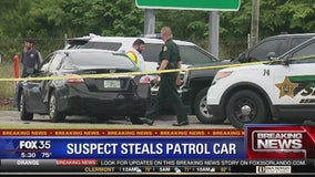 Bank robbery suspect dawns disguise and steals patrol car