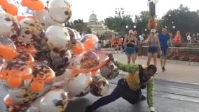 Wind almost carries away balloon handler at Mickey's Not-So-Scary Halloween Party