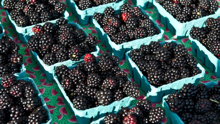 Blackberry quart containers on display at a farmers market.