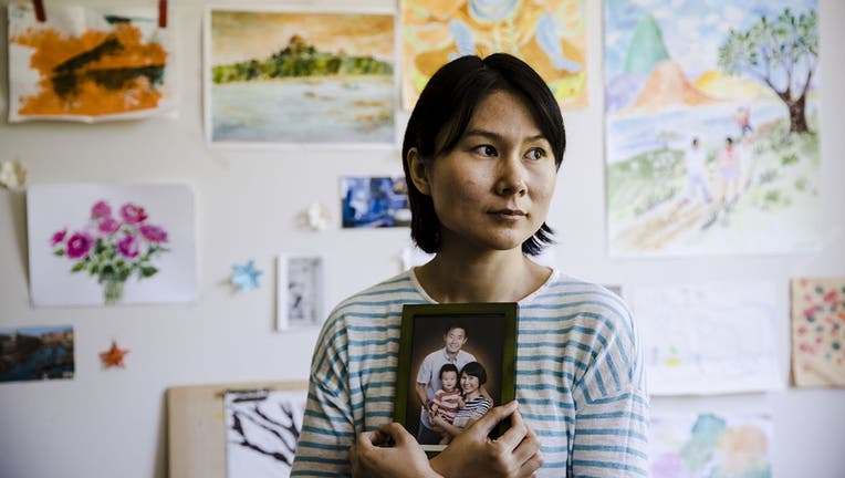 Hua Qu, the wife of detained Chinese-American Xiyue Wang, poses for a photograph with a portrait of her family in Princeton, New Jersey.