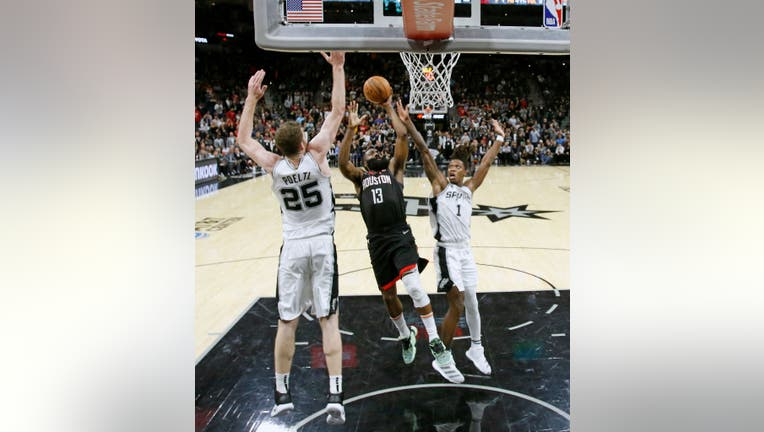 SAN ANTONIO, TX - DECEMBER 3: James Harden #13 of the Houston Rockets drives between Jakob Poeltl #25 of the San Antonio Spurs and Lonnie Walker #1 in the second half at AT&T Center on December 3, 2019 in San Antonio, Texas. NOTE TO USER: User expressly acknowledges and agrees that, by downloading and or using this photograph, User is consenting to the terms and conditions of the Getty Images License Agreement. (Photo by Ronald Cortes/Getty Images)