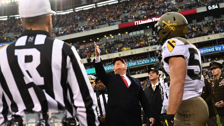 US President Donald Trump tosses the coin before the Army v. Navy American Football game in Philadelphia on December 14, 2019.
