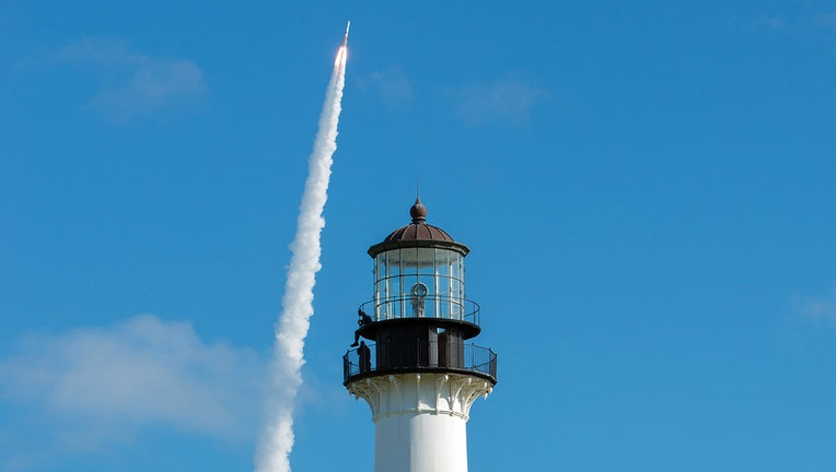United Launch Alliance's Delta IV GPS III Magellan rocket launches in the background of the Cape Canaveral Lighthouse on August 22, 2019, at Cape Canaveral Air Force Station. (U.S. Air Force photo by James Rainier)