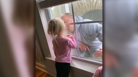 Quarantined firefighter kisses young daughter through closed window