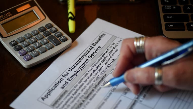 In this photo illustration, a person files an application for unemployment benefits on April 16, 2020, in Arlington, Virginia.