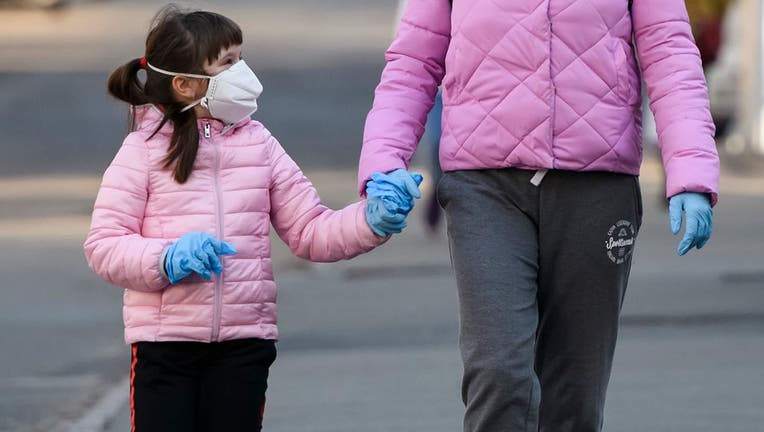 A woman and child are pictured in protective masks on a street in Kyiv, Ukraine on April 4, 2020.