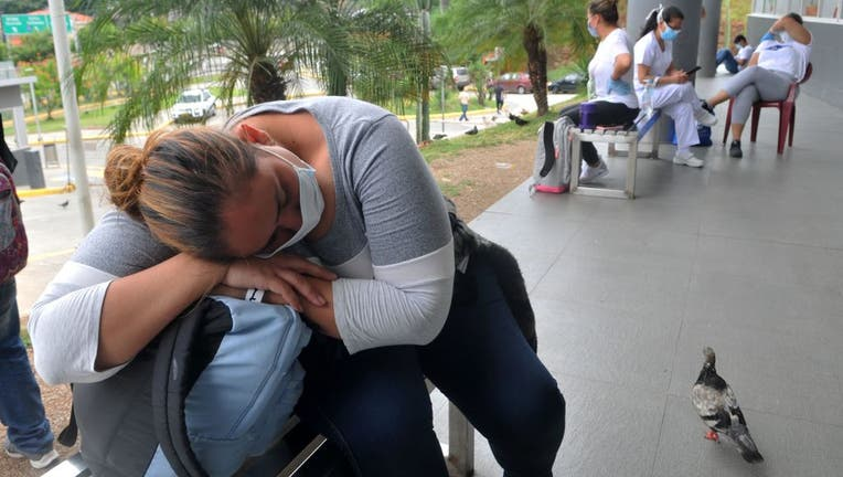 Relatives of patients being treated for COVID-19, wait for news of their loved ones at the IESS Hospital Los Ceibos in Guayaquil, Ecuador, on April 13, 2020 during the novel coronavirus pandemic.