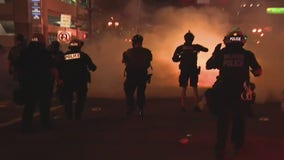 Orlando police officers fire tear gas at protesters to disperse crowds after curfew