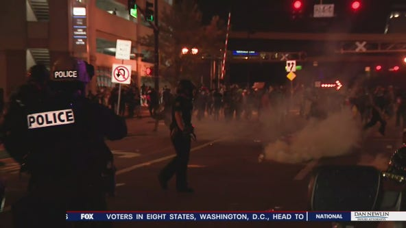 Police fire tear gas at protesters who respond by tossing water bottles