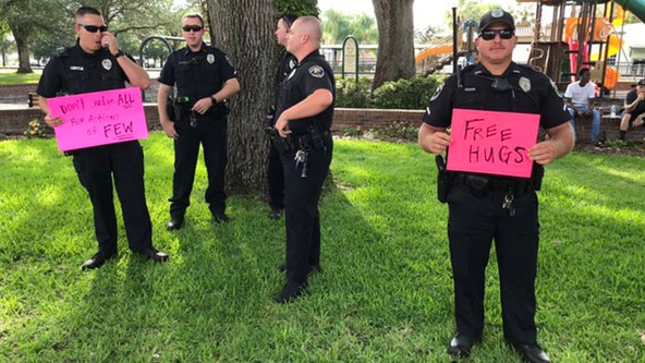 Officer holds 'free hugs' sign during peaceful protests in Polk County