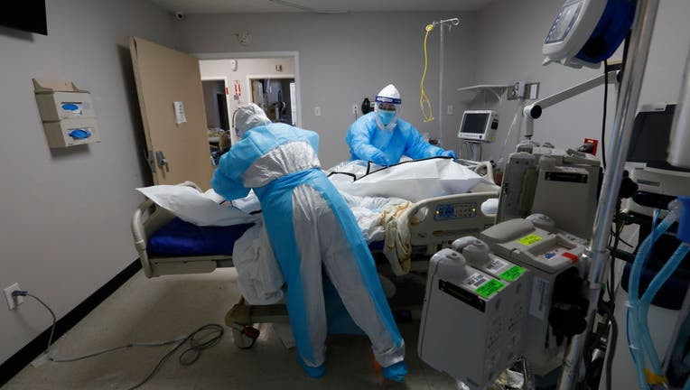 Dec. 9, 2020: Nurses ease a former COVID-19 patient into a body bag at a hospital in Houston, Texas. (Carolyn Cole / Los Angeles Times via Getty Images)