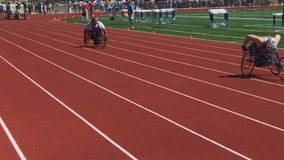 Coaches from both teams jump to help after wheelchair racer's tire breaks mid-race