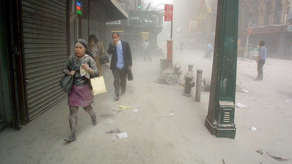 Pedestrians walk through soot after the