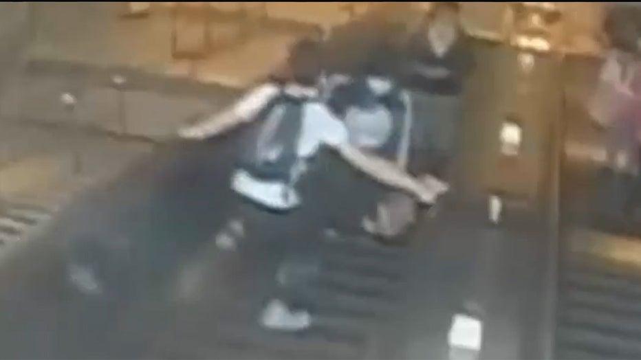 Man kicks woman on escalator