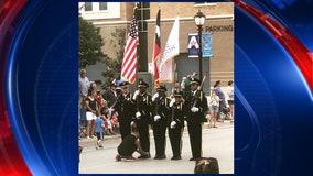 Boy ties shoe of Honor Guard member taking part in Arlington 4th of July parade