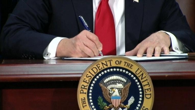 trump signs immigration order travel ban.jpg