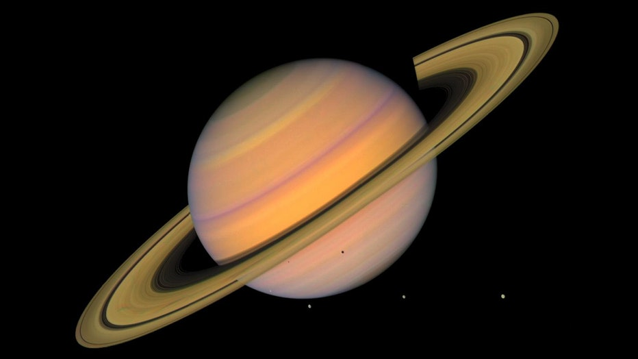 This approximate image shows Saturn, its rings, and four of its icy moons. Astronomers discovered 20 new moons orbiting the Ringed Giant this summer, making Saturn the planet with the most moons; Jupiter has 79.