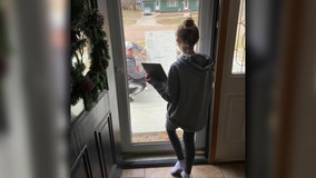 Math teacher brings over whiteboard to help student through glass door