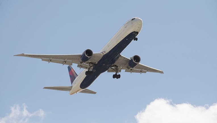 A Delta 767 400 passenger jet with landing gear down in preparation to land