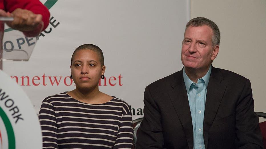 Chiara (left) and her father, Bill de Blasio (right), listen