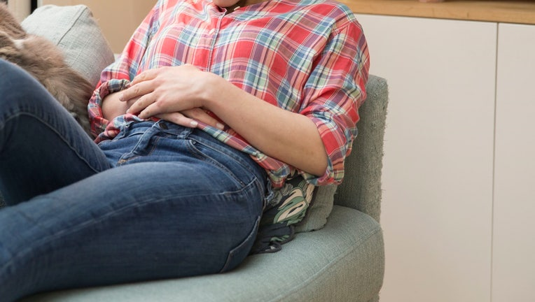 GettyImages-woman couch period abdominal pain