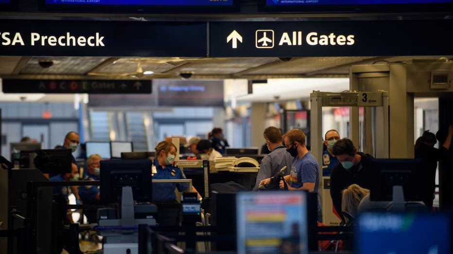 FILE - Travelers make their way through ticketing and TSA inspection as State of Pennsylvania remains under restrictions for work and travel at Pittsburgh International Airport.
