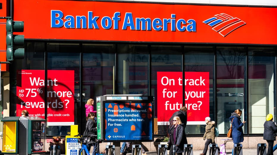 Pedestrians walk past a branch of Bank of America in New