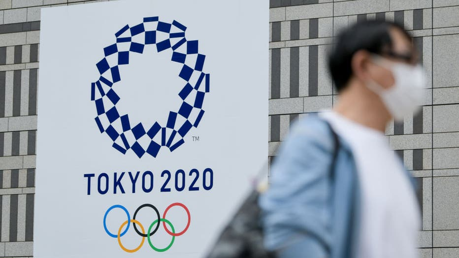 A man walks past a Tokyo 2020 banner on a building in