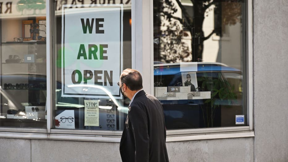 Man reads sign in business window that says,